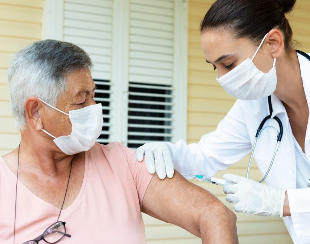 Woman gives vaccine to seated woman with mask